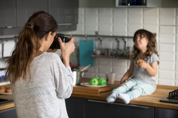 Young woman taking photo cute little preschool girl eating muffin in kitchen, mother photographing or shooting video daughter at home, family photo session, rear view