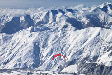 Paragliding at snowy mountains over ski resort at sunny winter day