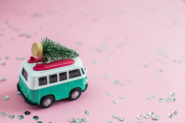 Riga, Latvia, October 31 2018. Hippie Bus with New Year Christmas Fir Tree on the Roof Miniature Small Car Banner Party Theme