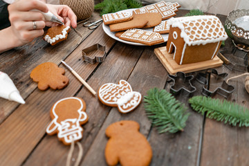 A young girl decorates ginger cookies in the form of star Christmas winter morning. Woman draws Icing on honey gingerbread cookies. Wooden brown table. copy space.