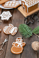 Cookies in the form of snowman Christmas winter morning. Woman draws Icing on honey gingerbread cookies. Wooden brown table. copy space.
