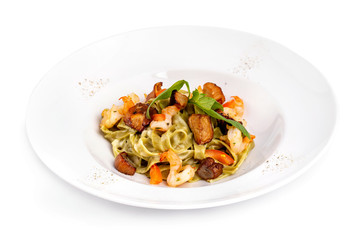 Plate of tasty seafood tagliatelle pasta with salmon and shrimps isolated at white background.