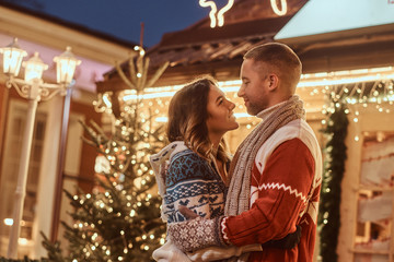 A young romantic couple wearing warm clothes hugging outdoor at Christmas time, standing in evening street decorated with beautiful lights.