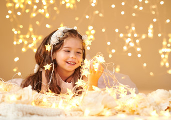 girl child is posing with christmas lights, yellow background, pink dress