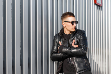 Handsome stylish young fashionable man in black leather jacket with black fashionable sweatshirt with sunglasses posing on the metal wall