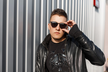 Stylish handsome young male hipster with sun glasses in a black leather stylish jacket with a black pullover near the metal wall.