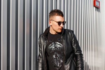 Stylish handsome fashionable young man hipster with sunglasses in black leather jacket and pullover near silver metal wall