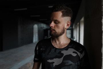 Handsome young man with a stylish hairstyle and brutal beard in a modern fashionable military t-shirt posing in a dark indoors. Attractive guy