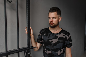 Pretty handsome hipster young man with a hairstyle and stylish beard in a fashionable military green camouflage T-shirt standing near the metal doors on a gray background. Fashionable attractive guy