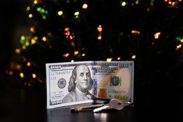 Key and banknote United States One Hundred Dollar under the new year tree