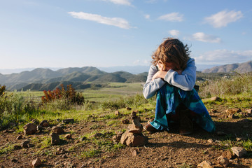Girl sitting on mountain against sky during sunny day