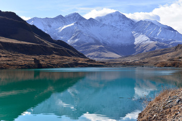 Beautiful turquoise lake in the middle of snow-covered mountains on a Sunny autumn day.