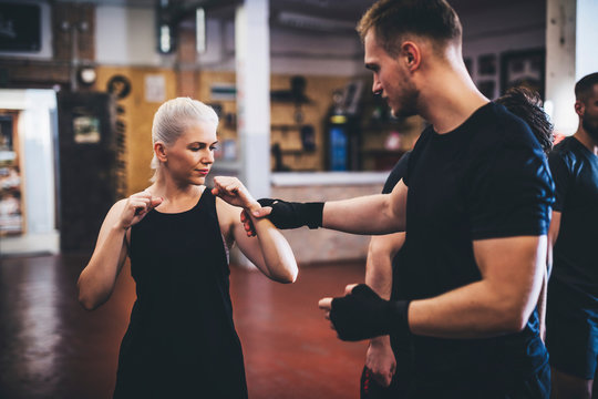 Coach teaching boxing to woman in gym