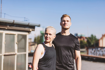Athlete couple looking away while standing at shipyard during sunny day