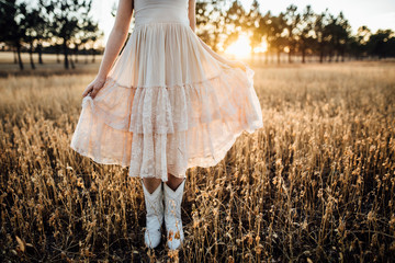 Low section of girl holding her dress while standing amidst plants on field during sunset Wall mural