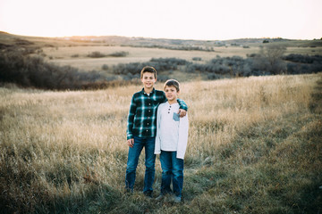 Full length portrait of brothers standing on field