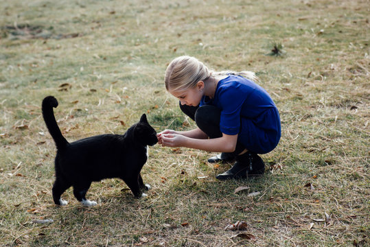Side view of girl playing with black cat while crouching on field