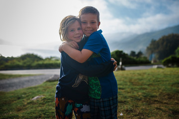 Portrait of smiling siblings embracing on field