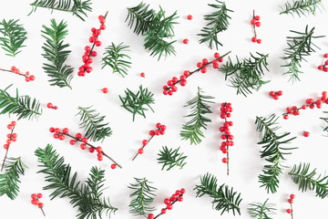 Christmas elegant modern composition. Coniferous tree branches and red natural berries on white background. Christmas, New Year, winter concept. Flat lay, top view, copy space