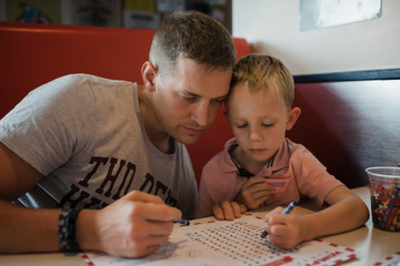 Father with son solving puzzle while sitting in restaurant