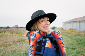 Portrait of happy woman with blanket wearing hat while standing on grassy field against clear sky