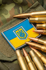 combat bullets on the background of the Ukrainian flag. Camouflage symbol of the Ukrainian army