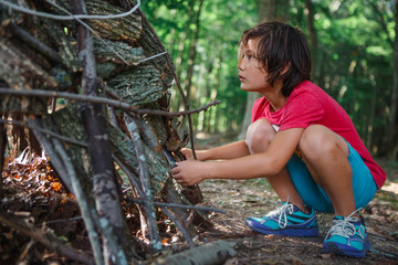 Boy making teepee with sticks while crouching in forest