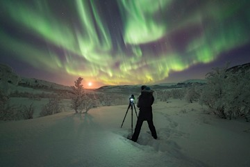 Photographer taking pictures of Northern Lights, Finland