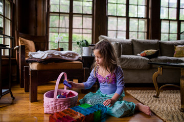 Girl wearing mermaid costume putting colorful tiles in basket at home