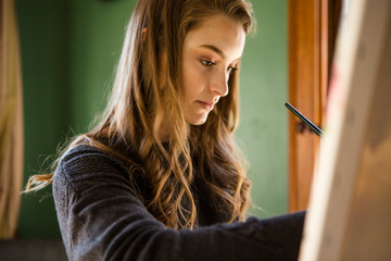 Close-up of woman painting on easel while standing in bedroom