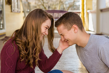Side view of happy sister touching brother's cheek while sitting in porch
