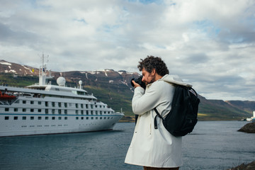 Trendy, millennial photographer in white raincoat or jacket and black hipster backpack makes photo of white cruise ship leaving port. New trend in tourism and travelling, explore iceland and norway