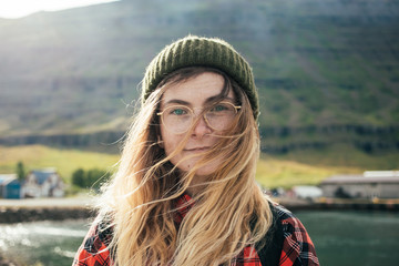 Portrait of young natural beautiful woman or girl with bright blue eyes and blonde hair in wind, wear green beanie and red hipster shirt, look at camera, gently smile