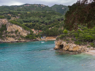 View on cllif and cave, trees and green hill at Paleokastritsa bay with two small boats summer cloudy sky, Corfu, Greece