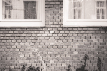 Brick wall texture of a house with white windows in black and white. Exterior of European style house with brick walls.
