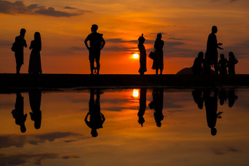 Silhouette of people visiting the Tanjung Aru beach during sunset located in Kota Kinabalu, Sabah, Malaysia.