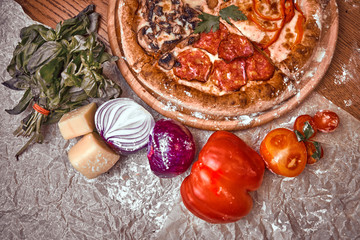 Pizza on wooden background with tomatoes, mushrooms,  basil and mozzarella cheese, close up top view