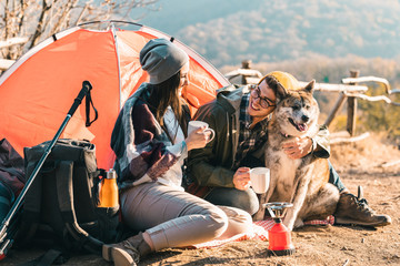 Young couple camping in the mountains with a dog