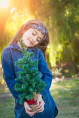Cute Mixed Race Young Girl Holding Small Christmas Tree Outdoors