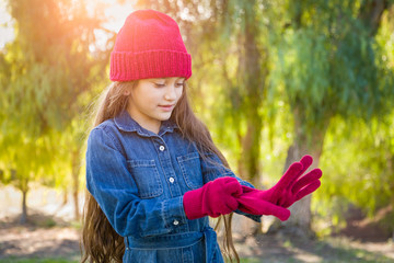 Cute Mixed Race Young Girl Wearing Red Knit Cap Putting On Mittens Outdoors
