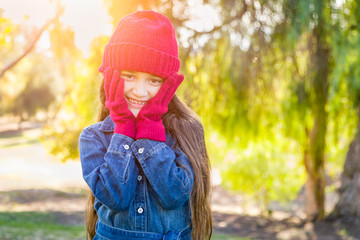 Cute Mixed Race Young Girl Wearing Red Knit Cap and Mittens Outdoors