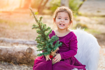 Cute Mixed Race Young Baby Girl Holding Small Christmas Tree Outdoors