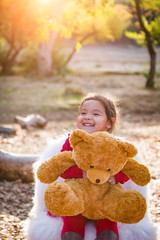 Cute Young Mixed Race Baby Girl Hugging Teddy Bear Outdoors