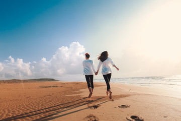 happy couple running on the beach.Young couple in love walking on the sand by the sea