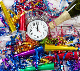 Happy New Year Celebration with clock in center of party objects on white rustic wooden boards