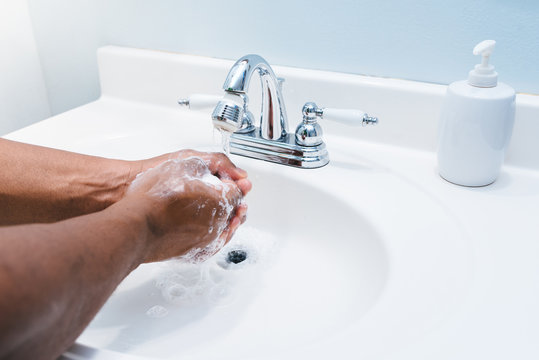 African american man washing hands in bathroom white sink and silver faucet