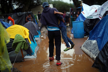 Migrants, part of a caravan of thousands from Central America trying to reach the United States, walk through a temporary shelter after heavy rainfall in Tijuana