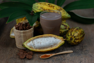 Fresh cacao fruit with cocoa crunch (Products Production from cacao) on table