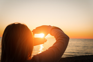 Hand reaching for sun. Sunset sun over the sea.