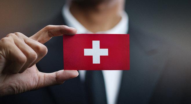 Businessman Holding Card of Switzerland Flag